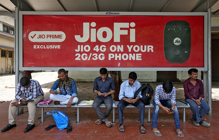 Commuters in Mumbai use their mobile phones as they wait at a bus stop with a telecom advertisement on July 10. The majority of India's internet users connect via their mobile devices. India recently adopted a rule that allows the government to temporarily shut down internet and telecommunications services in the event of an emergency. (Reuters/Shailesh Andrade)