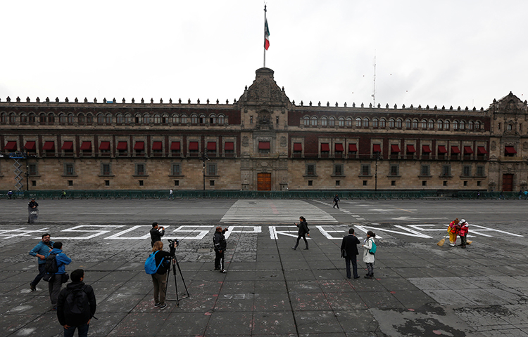 An activist puts on a window pictures of journalists who have been killed in Mexico during a demonstration against the murder of journalists in Mexico, outside the building of Attention to Crimes against Freedom of Expression (FEADLE) in Mexico City, Mexico on June 15, 2017. (Reuters/Edgard Garrido)