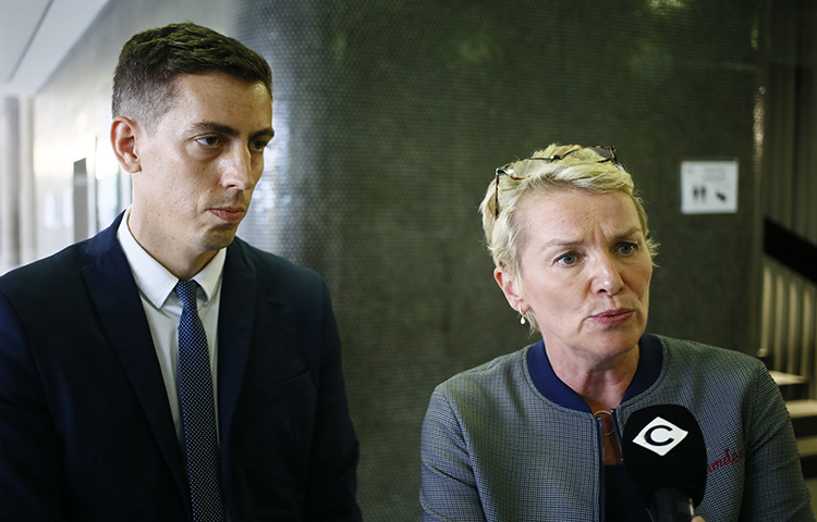 """French journalists Elise Lucet, right, and Laurent Richard answer reporters' questions outside a courtroom in a Paris suburb on September 5. Azerbaijan's government brought criminal defamation charges against the two journalists for calling the country a """"dictatorship."""" (AP/Francois Mori)"""
