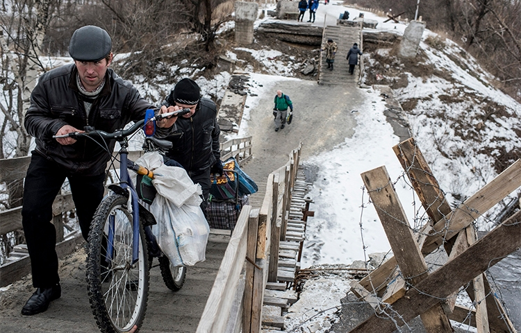 Residents cross a bridge damaged during fighting between Ukrainian government forces and Pro-Russian rebels near Luhanska, eastern Ukraine, in January 2016. Separatists are holding a blogger over his critical posts. (AP/Evgeniy Maloletka)