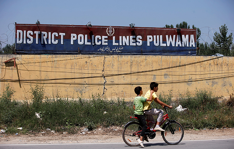 Boys ride past a police camp in the Pulwama district of the Jammu and Kashmir state. Photojournalist Kamran Yousuf, who frequently worked in this region, was arrested on accusations of stone throwing. (Reuters/Danish Ismail)
