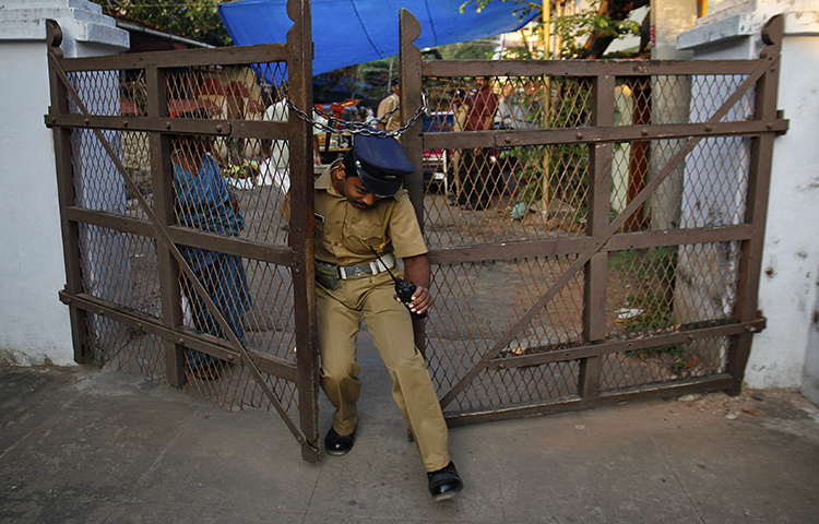 A policeman tries to enter through one of the gates in Sree Padmanabhaswamy temple complex in Thiruvananthapuram, capital of the southern Indian state of Kerala, February 20, 2012. A local newspaper filed a complaint with the Thiruvananthapuram rural district police after policeman allegedly attacked one of its journalists. (Reuters/Danish Siddiqui)