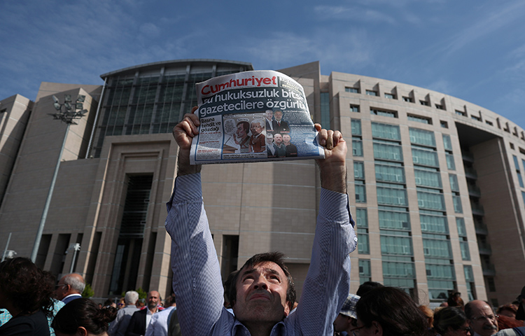 A press freedom activist holds a copy of the opposition newspaper Cumhuriyet during a demonstration in solidarity with the jailed members of the opposition newspaper outside a courthouse, in Istanbul on September 25. (Reuters/Osman Orsal)