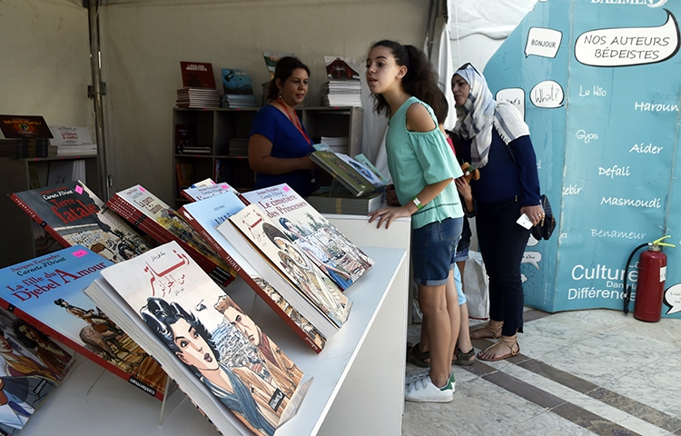 Women browse graphic novels at a comic festival in Algiers in October 2017. The co-founder of an Algerian news outlet says access to his news website is blocked. (AFP/Ryad Kramdi)