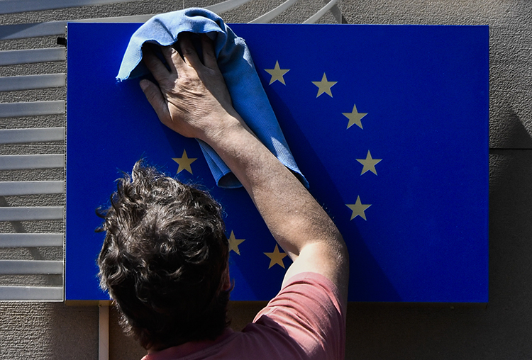 A worker cleans a EU flag in Berlin on May 19, 2017. The EU parliament is due to vote on October 12 on a proposed review mechanism of surveillance tool exports. (AFP/John MacDougall)