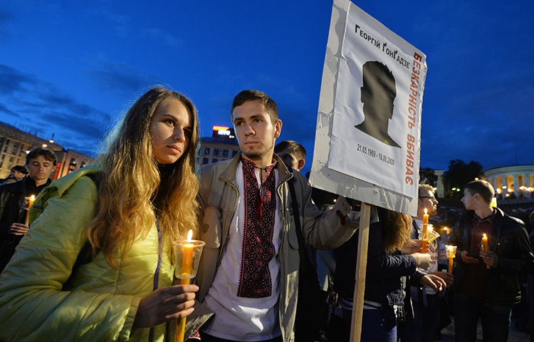 People hold signs saying 'Impunity kills' during a 2013 memorial in Kiev for murdered Ukrainian journalist Georgy Gongadze. The US decision to withdraw from UNESCO will make the world less safe for journalists. (AFP/Sergei Supinsky)