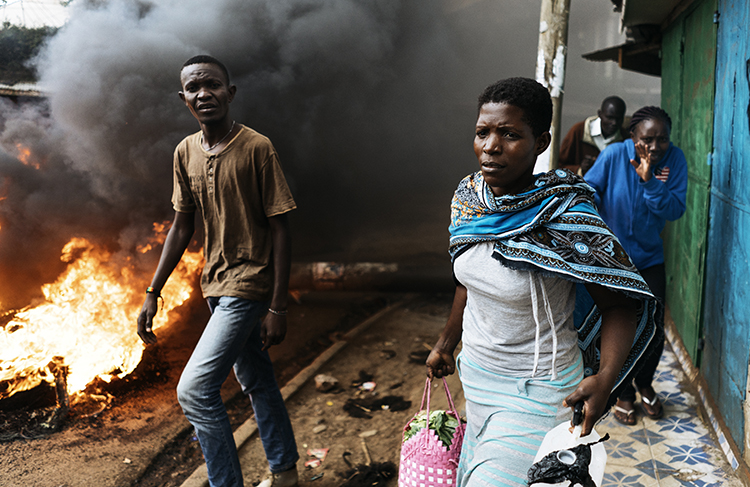 Residents pass a burning barricade in Kibera, Nairobi, on October 25, the day before presidential re-elections are held. Journalists covering the vote should take safety precautions. (AFP/Marco Longari)