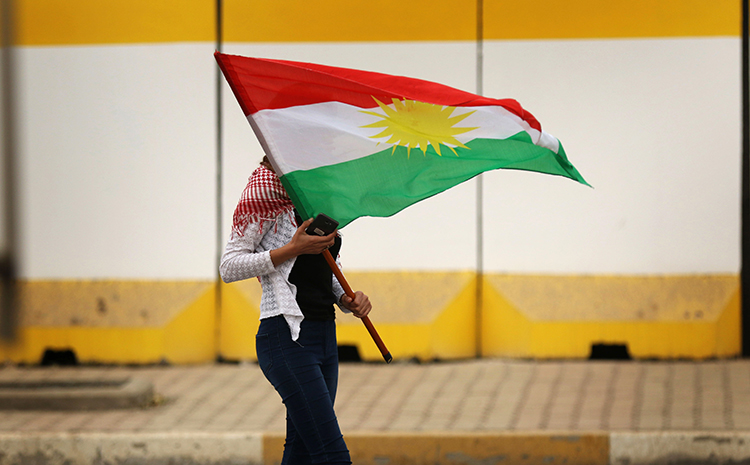 A Kurdish flag is waved during a rally in support of the Iraqi Kurdish leader in Erbil on October 30, 2017. Amid unrest in the region, Kurdish news outlets are attacked and harassed. (AFP/Safin Hamed)