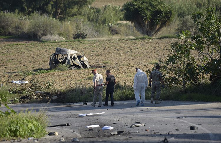 Police and forensic experts inspect the wreckage of a car bomb that killed journalist and blogger Daphne Caruana Galizia close to her home in Bidnija, Malta. (STR/AFP)