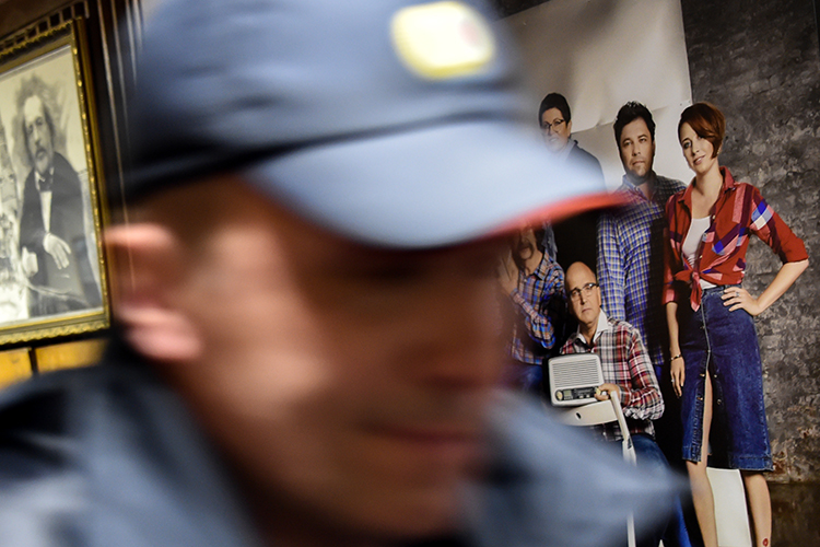 A police officer walks past a photograph of Ekho Moskvy journalists, including Tatyana Felgengauer, seen on the right, at the station's Moscow office. An assailant stabbed Felgengauer on October 23, 2017. (AFP/Vasily Maximov)