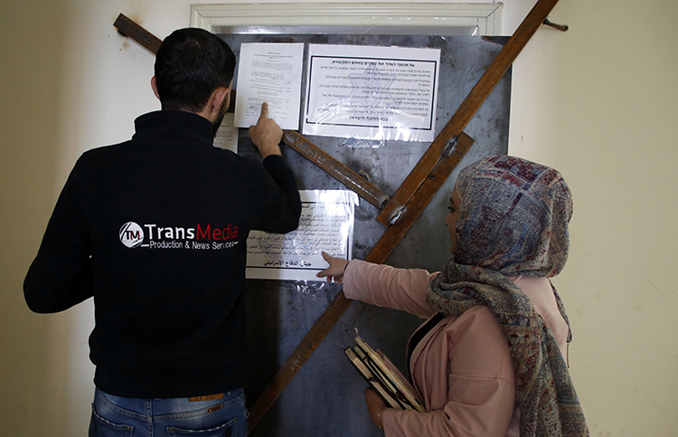 Employees of TransMedia look at a military order attached to their office doors in Hebron on October 18, 2017. Israeli forces raided several media companies for alleged incitement. (AFP/Hazem Bader)