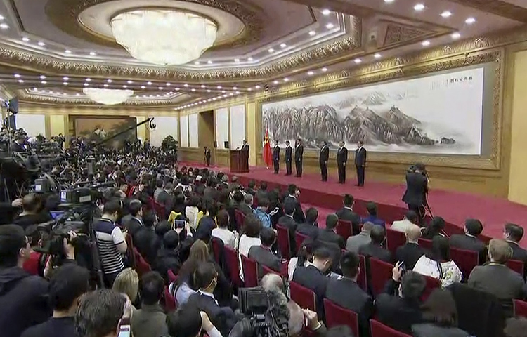 In this image made from video, Chinese President Xi Jinping, seventh from right on stage, introduces new members of the Politburo Standing Committee to the media at Beijing's Great Hall of the People on October 25, 2017. (APTN via AP)