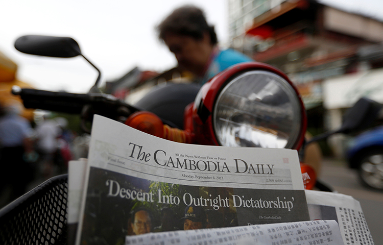 A woman buys the final issue of the Cambodia Daily newspaper at a store in Phnom Penh, Cambodia, September 4, 2017. (Reuters/Samrang Pring)