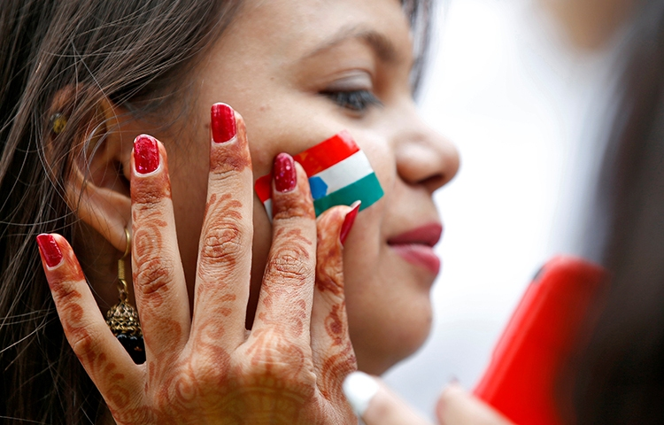 An Indian flag is painted on a woman's face during rehearsals for India's Independence Day celebrations in Ahmedabad. A court in the city issued an injunction against the news website The Wire. (Reuters/Amit Dave)