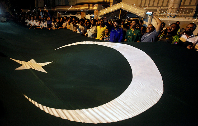 Pakistan's cricket fans wave a national flag in Karachi, Pakistan on June 20, 2017. Pakistan's interior ministry ordered he Interior Ministry on January 19, 2018 ordered the Pashto-language service of U.S. Congress-funded Radio Free Europe/Radio Liberty, Radio Mashaal, to close immediately. (Reuters/Akhtar Soomro)