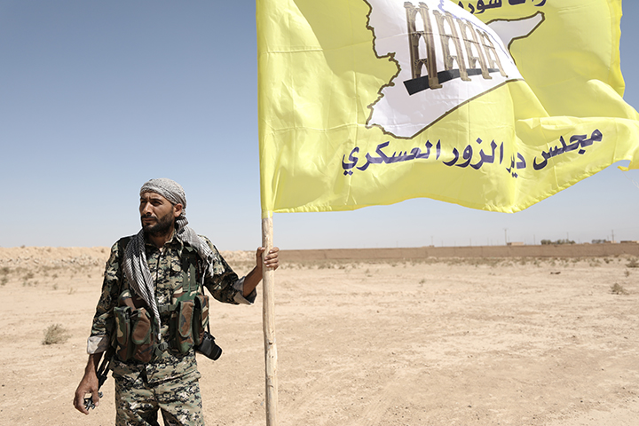 A fighter from Deir al-Zor military council which fights under the Syrian Democratic Forces holds the council's flag in the village of Abu Fas, Hasaka province, Syria September 9, 2017. Two reporters died in car bombing attacks on October 12 in Abu Fas. (Reuters/Rodi Said)