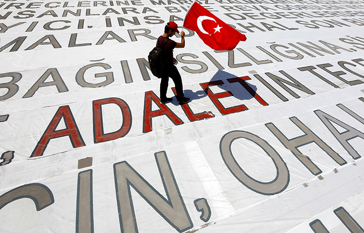 A young man on July 9 with a Turkish flag during a rally in Istanbul to mark the end of a 25-day-long protest against the detention of lawmaker Enis Berberoglu. The word in red means justice. (Reuters/Umit Bektas)