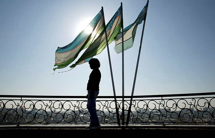 A girl is silhouetted against the sun standing next to Uzbek flags in Tashkent. Uzbek journalist Bobomurod Abdullaev went missing on September 27, 2017, and has since been secretly tried in a criminal court in Tashkent. (Reuters/Shamil Zhumatov)