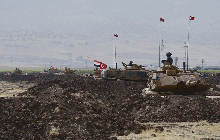 Turkish and Iraqi soldiers sit on Turkish tanks during exercises in Silopi, southeastern Turkey, near the border with Iraq, on September 26, 2017. A Wall Street Journal reporter is convicted of terrorism charges for her reporting from the area.(DHA-Depo Photos via AP )
