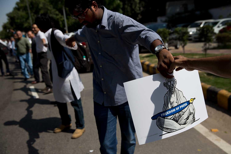 صحفيون هنود يشكلون سلسلة بشرية قرب نادي الصحافة الهندي في 2 أكتوبر/ تشرين الأول 2017، وذلك احتجاجاً على مقتل صحفيين في نيودلهي. وقد جرت جميع جرائم قتل الصحفيين في الهند بإفلات تام من العقاب. (أسوشيتد برس/ تسيرينغ توبغيال)