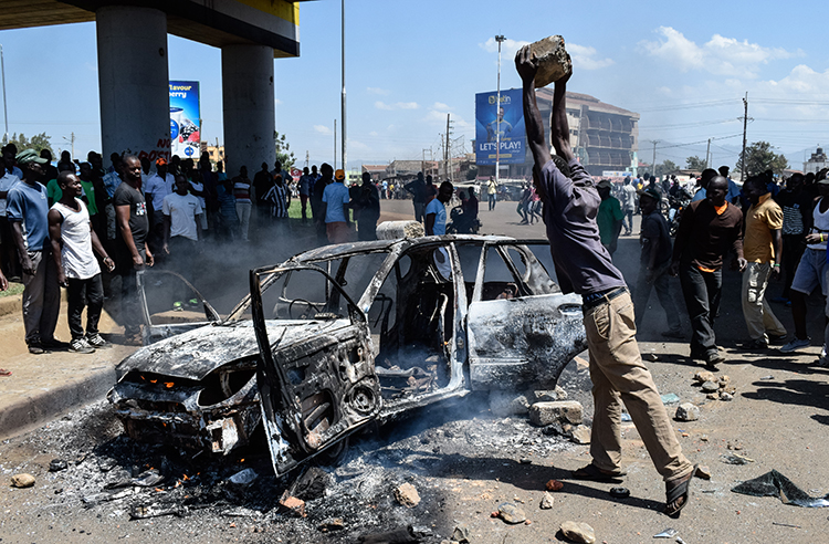 A man throws a stone on a burnt car during clashes in Kisumu on November 20 over Kenya's Supreme Court ruling on the country's election. (AFP/Brian Ongoro)