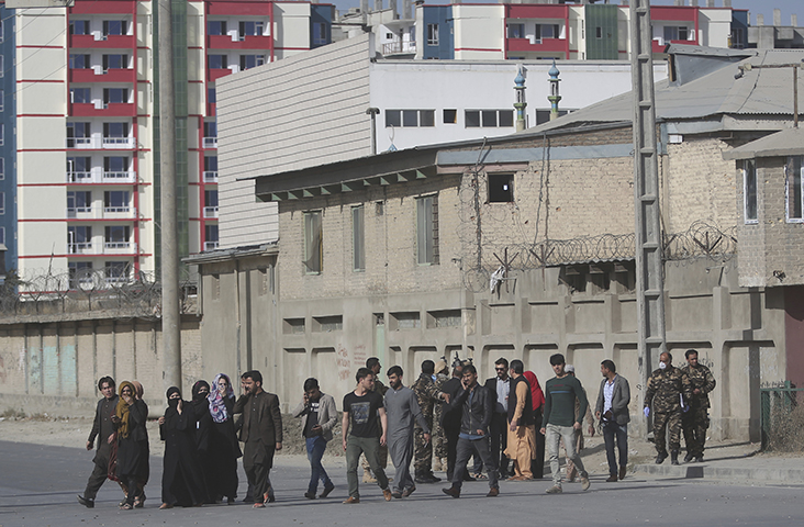 Security personnel evacuate employees of the Shamshad TV building after an attack in Kabul, Afghanistan, Tuesday, Nov. 7, 2017. (AP/Massoud Hossaini)