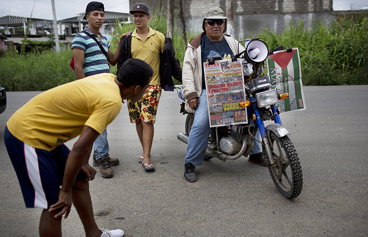 A vendor waits for customers while selling newspapers on his motorcycle, one week after an earthquake in Pedernales, Ecuador. A local journalist says years of self-censorship among the press led to 'timid' early reports of the disaster. (AP/Rodrigo Abd)