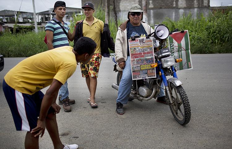 """Un vendedor espera a los clientes mientras vende periódicos en su motocicleta, una semana después de un terremoto en Pedernales, Ecuador. Un periodista local dice que los años de autocensura entre la prensa provocaron informes preliminares """"tímidos"""" sobre el desastre. (AP/Rodrigo Abd)"""
