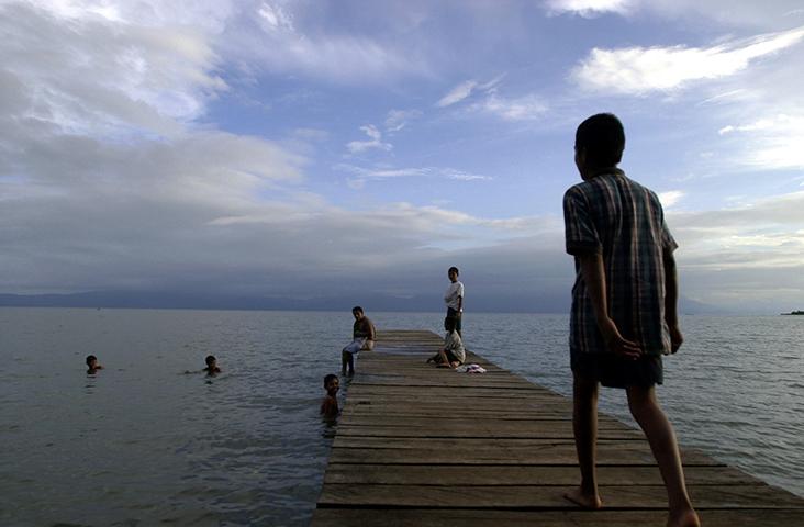 Crianças brincam no lago Izabal, na Guatemala, nesta fotografia de agosto de 2002. A polícia local, em 11 de novembro de 2017, prendeu Jerson Antonio Xitumul Morales, repórter da mídia digital independente Prensa Comunitaria, depois que ele informou sobre os protestos de uma associação de pescadores na província de Izabal. (AP/Jaime Puebla)