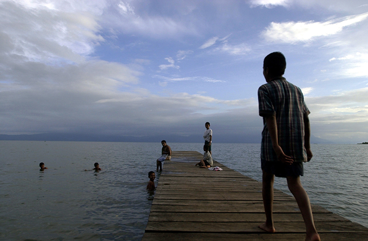 Children play in the Izabal Lake in Guatemala in this photograph from August 2002. Local police on November 11, 2017, arrested Jerson Antonio Xitumul Morales, a reporter with the independent digital media outlet Prensa Comunitaria, after he reported on a local fishermen guild's protests in the Izabal province. (AP/Jaime Puebla)