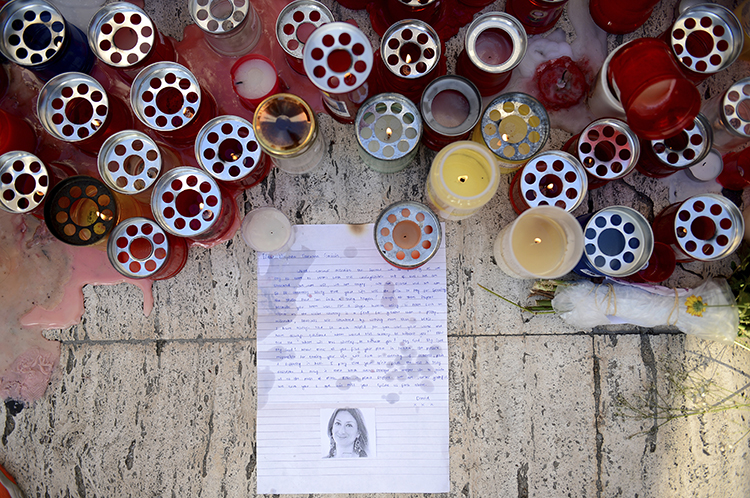 Candles and tributes are left for investigative journalist Daphne Caruana Galizia, who was murdered in Malta in October, (AP/ Rene Rossignaud)