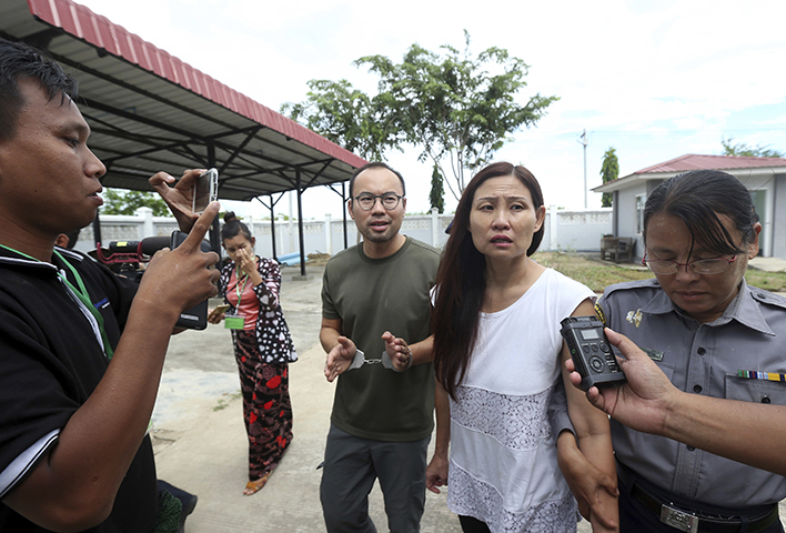 Singaporean journalist Lau Hon Meng, center left, and Malaysian journalist Mok Choy Lin, both accused for allegedly flying drones illegally over parliament buildings, are escorted during their trial at a court Friday, Nov. 10, 2017, in Naypyitaw, Myanmar. (AP/Aung Shine Oo)