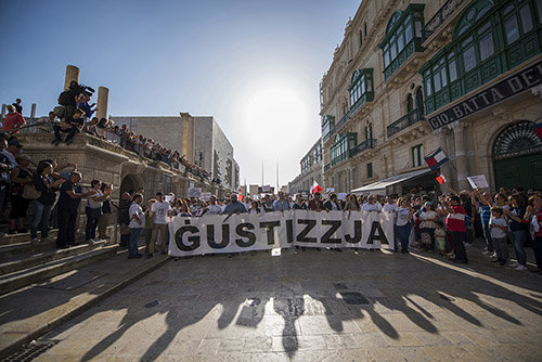A rally in Malta to honor Daphne Caruana Galizia, an investigative journalist who was killed in October. The sign reads JUSTICE. (AP/Rene Rossignaud)