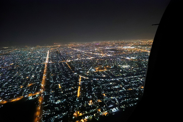 The city of Baghdad is seen out the door during a helicopter on October 23, 2017. Iraqi armed forces arrested freelance journalist and political commentator Samir Obeid a day after Obeid published an article that was critical of the country's prime minister. (Reuters/Pool/Alex Brandon)