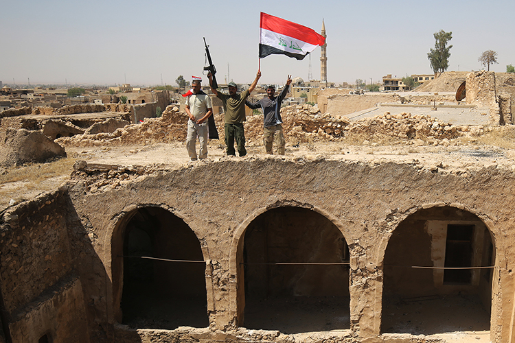 Members of the Popular Mobilisation Units pose with the Iraqi flag in Tal Afar. Authorities in Iraq and Syria who relied on militias to help fight Islamic State must now decide what to do with the groups. (AFP/Ahmad al-Rubaye)