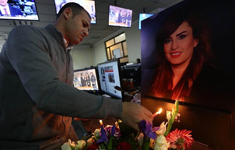 Um colega da repórter iraquiana Shifa Gardi acende uma vela em uma vigília para ela na redação da Rudaw TV em Erbil. O Iraque foi o país mais letal para jornalistas em 2017. (AFP / Safin Hamed)