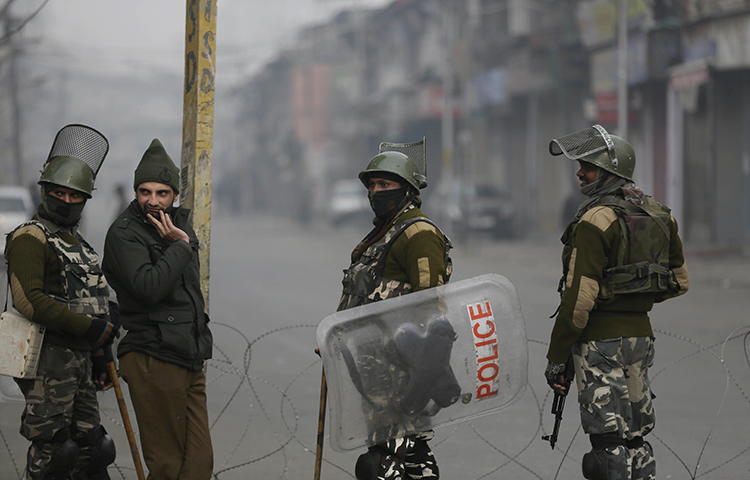 Indian paramilitary soldiers and a policeman, second from left, guard a checkpoint during a strike to mark International Human Rights Day in Srinagar, India, on December 10, 2017. State police arrested french filmmaker Comiti Paul Edwards on December 9, in Srinagar while he was shooting a documentary on people injured by pellet guns. (AP/Mukhtar Khan)