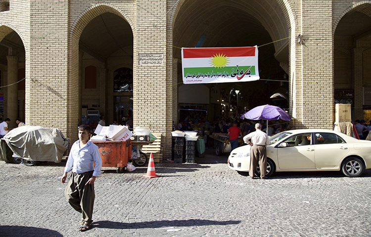 In this Thursday, Aug. 24, 2017 photo, a man walks past a campaign poster printed on a Kurdish flag urging people to vote yes in the poll on independence from Iraq, Irbil, Iraq. The Committee to Protect Journalists today condemned theclosure of an independent television broadcaster by the Kurdish authorities in northernIraq, and attacks on journalists covering anti-austerity protests held yesterday in thesame region.(AP/Balint Szlanko)