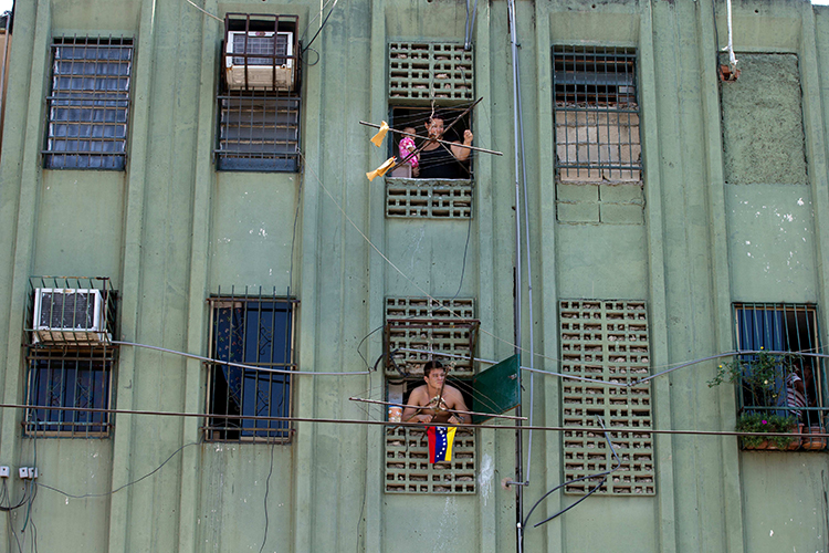 Residents in a Valencia apartment block watch a rally on the street below in March 2014. Several of the city's critical newspapers have been forced out of circulation amid Venezuela's economic crisis and newsprint shortage. (AP/Fernando Llano)