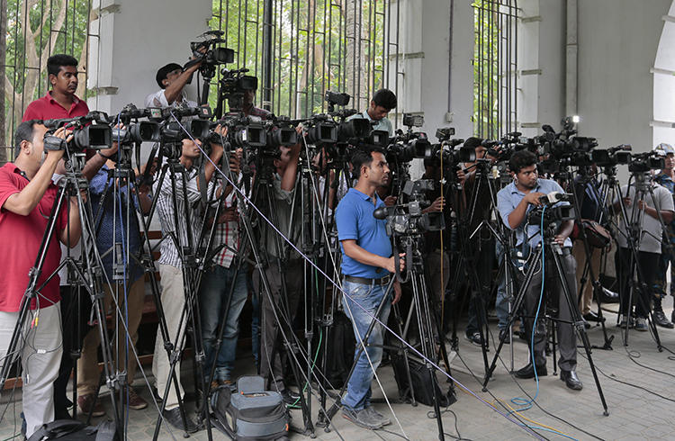 Bangladeshi journalists cover proceedings outside a Dhaka court in May 2016. The country's vaguely worded defamation law is creating a climate of self censorship, local reporters say. (AP/A.M. Ahad)