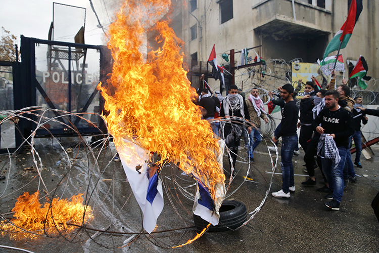 Protesters burn an Israeli flag in front of the U.S. Embassy in Lebanon, during a demonstration in Aukar, east of Beirut, on December 10. Rallies are being held in several countries after President Donald Trump said he will recognize Jerusalem as Israel's capital. (AP/Bilal Hussein)