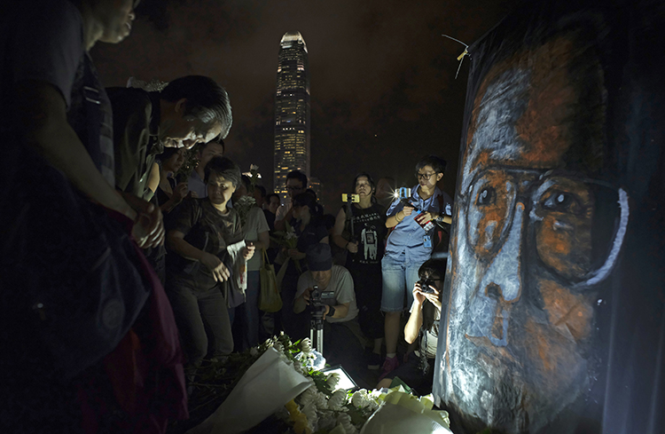 People pay tribute to Nobel laureate Liu Xiaobo in a park near Hong Kong's Victoria Habour in July 2017. The journalist died a few months after China finally agreed to release him on medical parole. (AP/Vincent Yu)