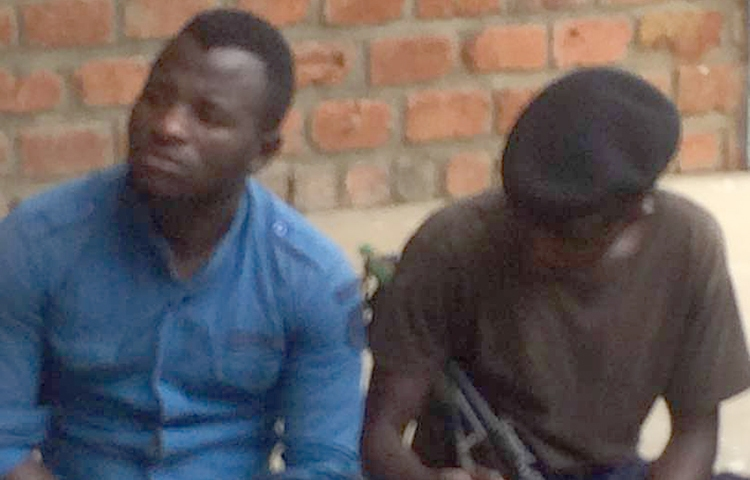 DRC journalist Benjamin Mutiya, left, pictured under police guard on December 18, is detained on defamation accusations. (Fortunat Maronga/CJDH)