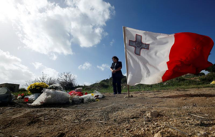 Tributes and a flag are left at the spot where investigative journalist Daphne Caruana Galizia was killed in a bombing in October. Police in Malta arrested 10 suspects in the case on December 4. (Reuters/Darrin Zammit Lupi)