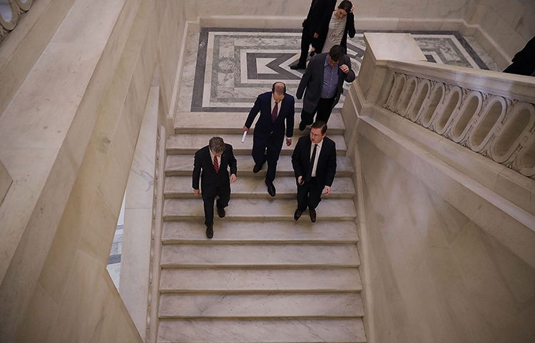 Senators talk together in the the Russell Senate Office Building after leaving a January 16 news conference about proposed reforms to FISA. The Senate has reauthorized Section 702 of the act in a move that could put journalists at risk. (Chip Somodevilla/Getty Images/AFP)