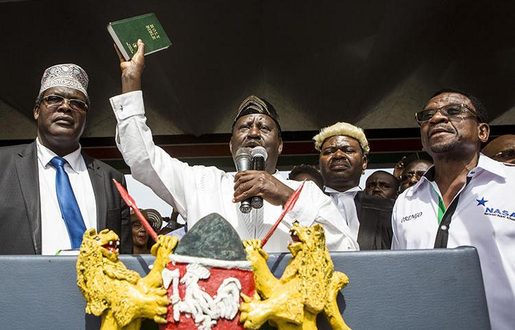 Kenya's opposition coalition leader Raila Odinga holds a bible as he declares himself the 'people's president' in Nairobi on January 30. Authorities cut the transmissions to four broadcasters over their attempted live coverage of the event. (AFP/Patrick Meinhardt)