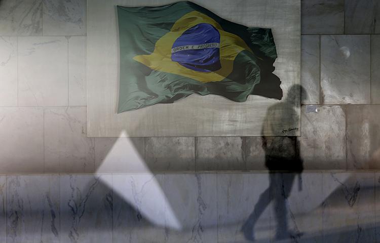Una guardia presidencial pasa frente a una ventana con una vista del salón principal del palacio presidencial de Planalto, decorado con una imagen de la bandera nacional brasileña, en Brasilia, Brasil, el 13 de abril de 2017. (AP / Eraldo Peres)