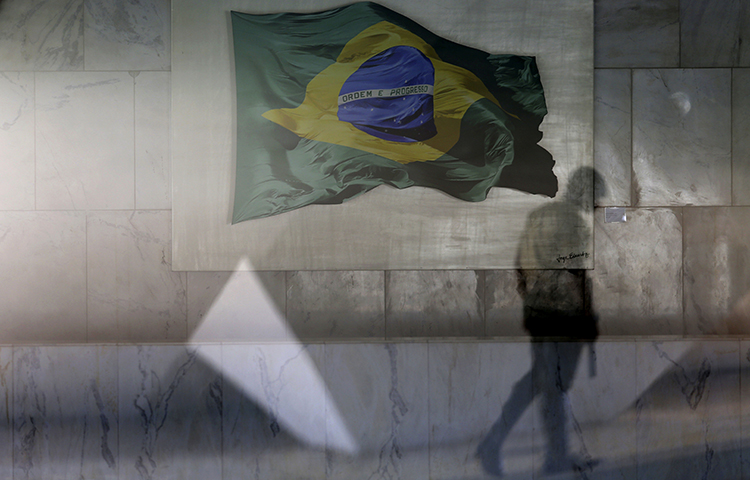 A presidential guard walks past a window that allows a view into the Planalto presidential palace's main lounge, decorated with an image of a Brazilian national flag, in Brasilia, Brazil, Thursday, April 13, 2017. (AP/Eraldo Peres)