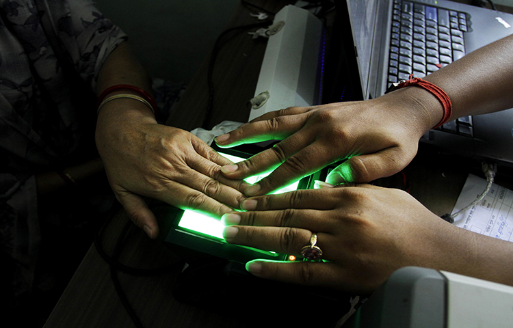 In this May 16, 2012 file photo, an operator helps an elderly woman scan her fingerprints as she enrolls for Aadhar, India's unique identification project in Kolkata, India. The country's leading English-language daily, The Tribune, published an article exposing a possible vulnerability in the system. (AP/Bikas Das)