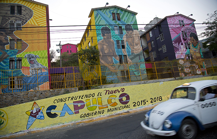 """A taxi drives past the Cuauhtemoc Housing Unit and a municipal sign with a message that reads in Spanish """"Building the new Acapulco"""" in Acapulco, Mexico on May 11, 2016. Antonio Julián Chepe said he was driving his vehicle on the highway between his hometown in Marquelia and Acapulco in Mexico's southern Guerrero state when at least six men carrying automatic rifles attacked him. (AP/ Enric Marti)"""